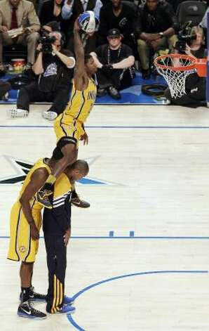 Indiana Pacers' Paul George jumps over two teammates on his attempt during the NBA basketball All-Star Slam Dunk Contest in Orlando, Fla., Saturday, Feb. 25, 2012. (AP Photo/Chris O'Meara) (AP) / SA