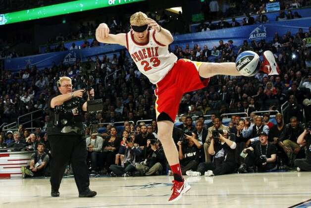 Houston Rockets' Chase Budinger follows through on a blindfolded dunk in honor of former Phoenix Suns' Cedric Ceballos, who performed a blindfolded dunk in 1992, during the NBA basketball All-Star Slam Dunk contest, Saturday, Feb. 25, 2012, in Orlando, Fla. (AP Photo/Lynne Sladky) (AP) / SA
