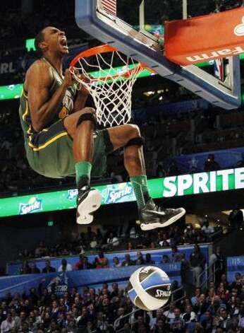 Utah Jazz's Jeremy Evans hangs onto the rim after his attempt during the NBA basketball All-Star Slam Dunk Contest in Orlando, Fla., Saturday, Feb. 25, 2012. Evans earned 29 percent of 3 million text message votes cast by fans to win the competition. (AP Photo/Lynne Sladky) (AP) / SA