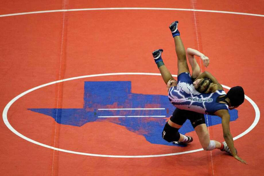 Diaysha Moore of Cy Ridge is slammed to the mat by Shelby Morrison of Bushland during the girls 119-pound weigh class finals during the UIL State Wrestling Tournament at the Delco Center,  Saturday, Feb. 25, 2012, in Austin. Photo: Smiley N. Pool, Houston Chronicle / © 2012  Houston Chronicle