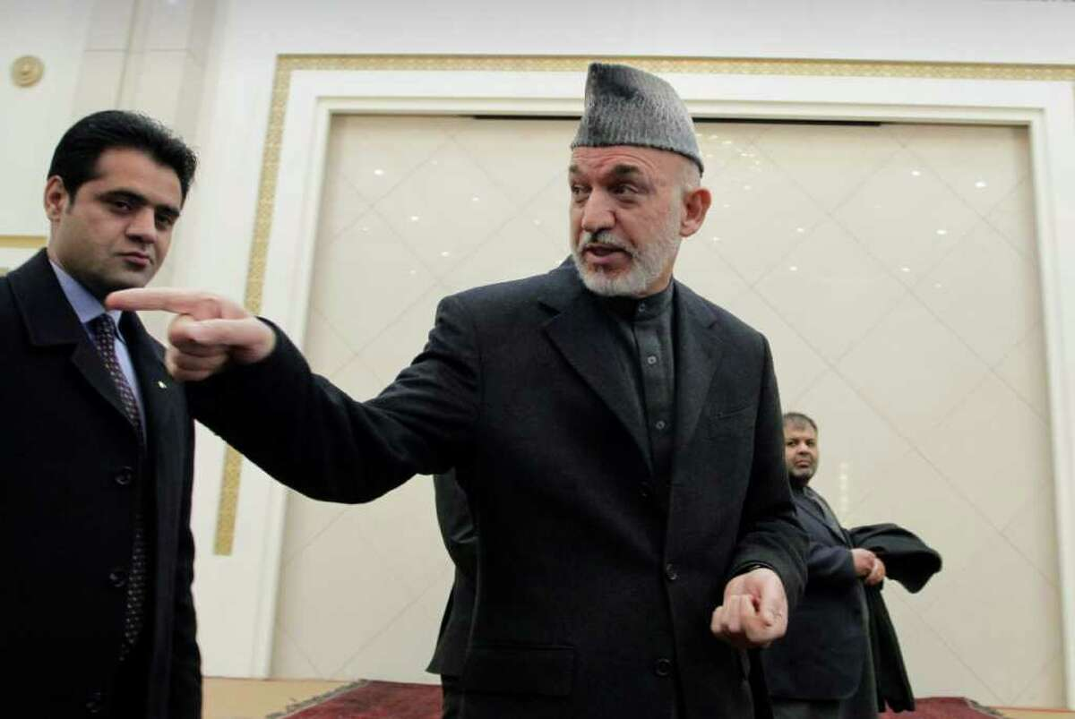 Afghan President Hamid Karzai gestures toward a journalist, not pictured, at the end of his press conference at the presidential palace in Kabul, Afghanistan, Sunday, Feb. 26, 2012. Afghanistan's president renewed his calls for calm Sunday in a televised address to the nation after the burning of Qurans at a U.S. base sparked five days of deadly protests and prompted the international military coalition to pull its advisers from Afghan ministries out of fear that they would become the next targets.