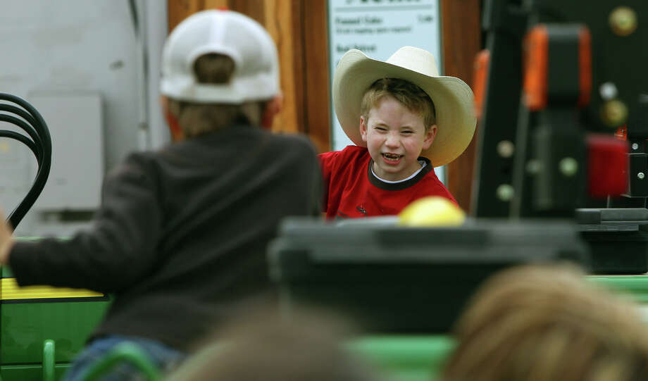 Cason Griffith,7, (facing) plays on a tractor with his friend Stockton Shannon,6, (facing away, left) on the last day of the San Antonio Stock Show & Rodeo. Both boys are from Del Rio, Texas. (Sunday February 26, 2012. John Davenport/San Antonio Express-News Photo: JOHN DAVENPORT, SAN ANTONIO EXPRESS-NEWS / SAN ANTONIO EXPRESS-NEWS (Photo can be sold to the public)