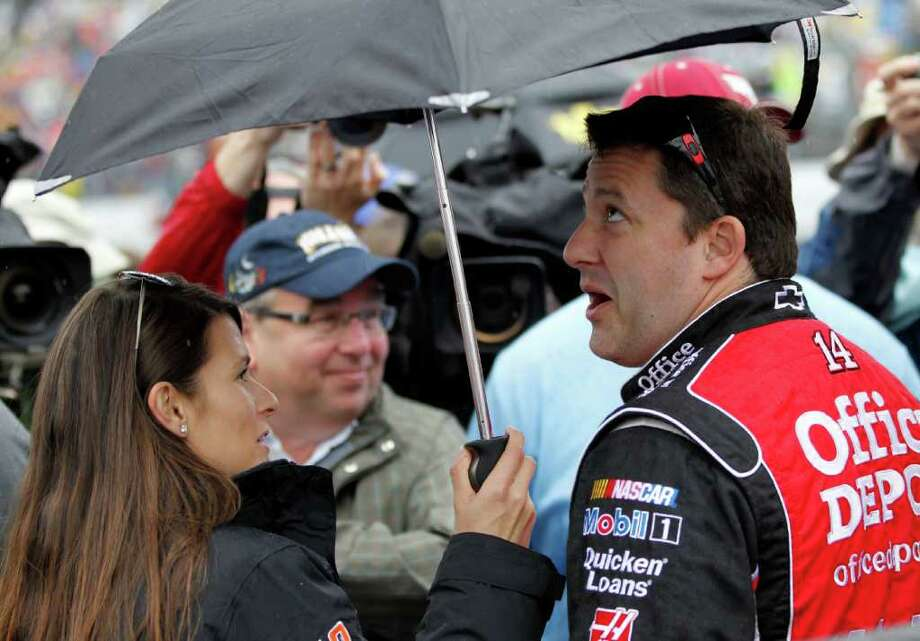 Danica Patrick and Tony Stewart stand under an umbrella before the Daytona 500 was postponed Sunday. Photo: AP