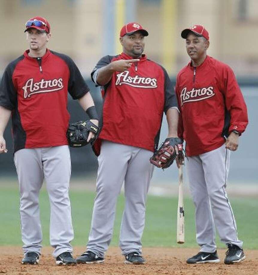 Astros third baseman Chris Johnson and infielder Carlos Lee chat with first base coach Bobby Meacham. (Karen Warren / Chronicle)