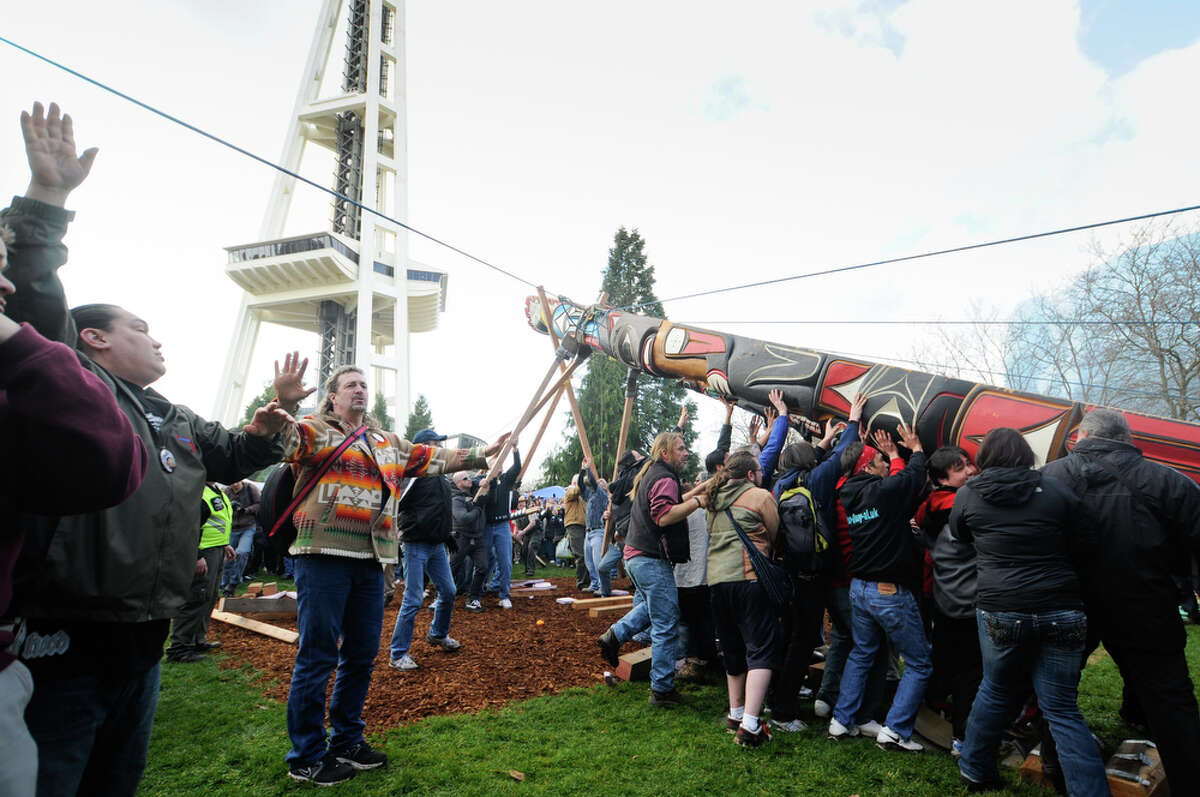 People help erect the totem pole carved in honor of slain woodcarver John T. Williams near the Space Needle on Sunday, Feb. 26, 2012. At 33 feet tall and roughly 5,000 pounds, the totem pole was carried by supporters from Pier 57 to a plaza at Seattle Center, where it was erected.