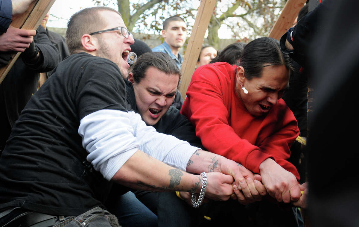 A group of men struggle as they help secure totem pole carved in honor of slain woodcarver John T. Williams on Sunday, Feb. 26, 2012. At 33 feet tall and roughly 5,000 pounds, the totem pole was carried by supporters from Pier 57 to a plaza at Seattle Center, where it was erected.