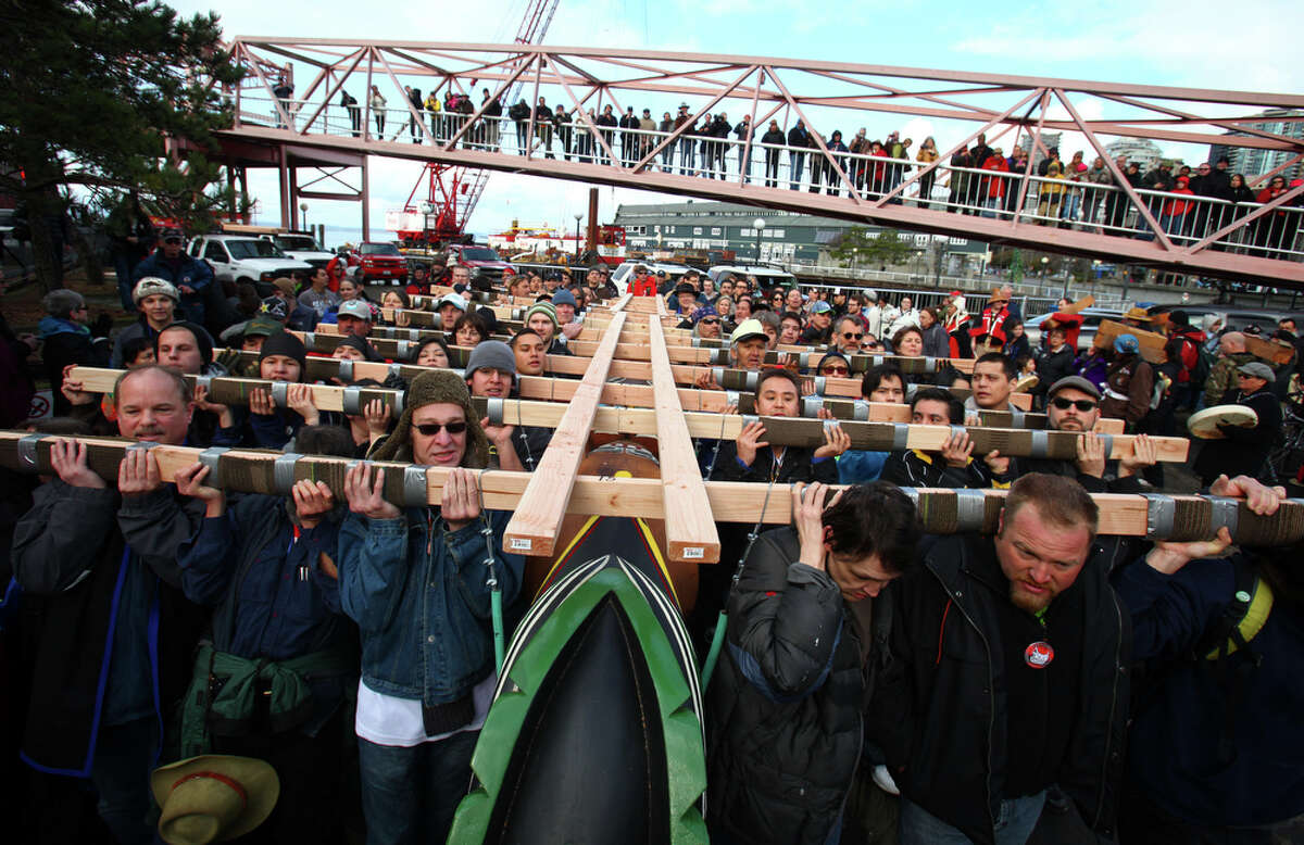 People carry a totem pole estimated to weigh nearly 5,000 pounds during a procession to the Seattle Center from pier 57 on Sunday February 26, 2012 in Seattle. The 33-foot tall totem pole was erected Sunday in honor of slain Native American woodcarver John T. Williams. Williams was shot and killed by a Seattle Police officer in 2010. The shooting was later ruled unjustified.