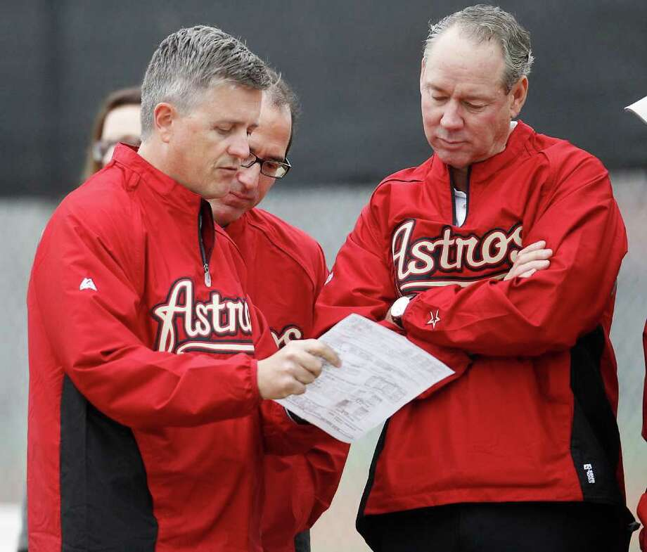 Astros general manager Jeff Luhnow, left, CEO George Postolos, center, and owner Jim Crane talk Sunday about the team's daily activities. Photo: Karen Warren / © 2012  Houston Chronicle