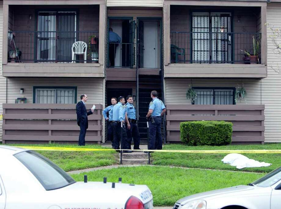 Houston Police officers investigate at the scene of a murder-suicide at an apartment complex in the 6100 block of Reims on Sunday. The body of the shooter, the father of two girls, lies under the white sheet at right. Photo: James Nielsen / © 2011 Houston Chronicle