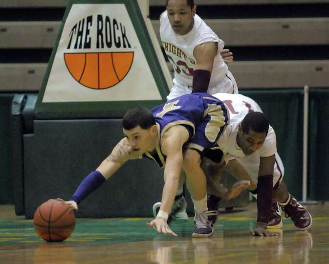 Hector Julia  of Amsterdam, left, battles for loose ball against Bishop Gibbons players  during thei