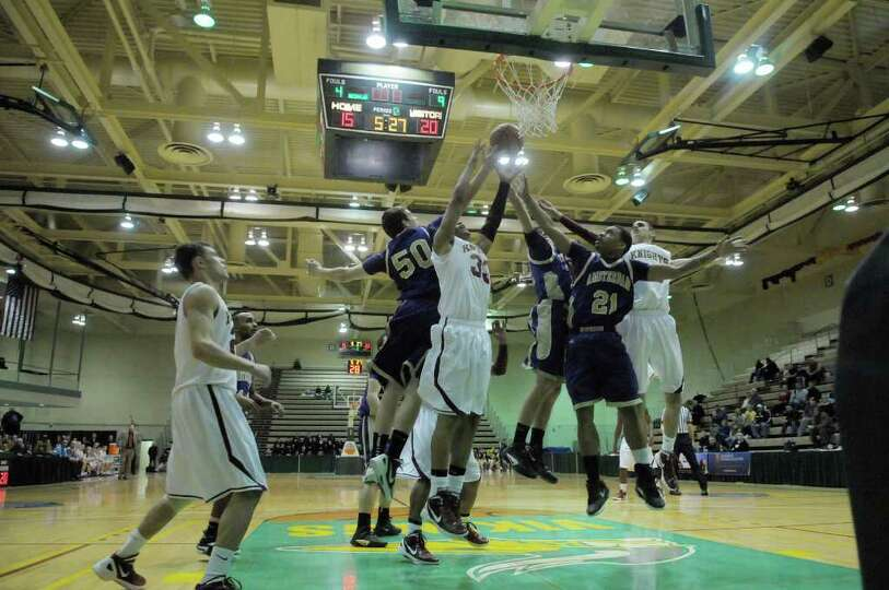 Bishop Gibbons and Amsterdam players go up for a rebound during their Class A boys' basketball quart