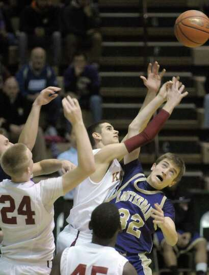 Kyle Garrison of Bishop Gibbons, center, and John Hardies  of Amsterdam, right, fight for a rebound