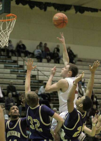 Imre Megyeri  of Bishop Gibbons puts up a shot over Amsterdam players during their Class A boys' bas