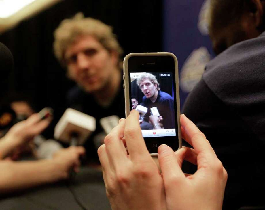 A reporter captures video as Dallas Mavericks' Dirk Nowitzki speaks during an NBA All Star basketball player news conference, Friday, Feb. 24, 2012, in Orlando, Fla. The NBA All Star game will be played in Orlando on Sunday. (AP Photo/Chris O'Meara) Photo: Associated Press