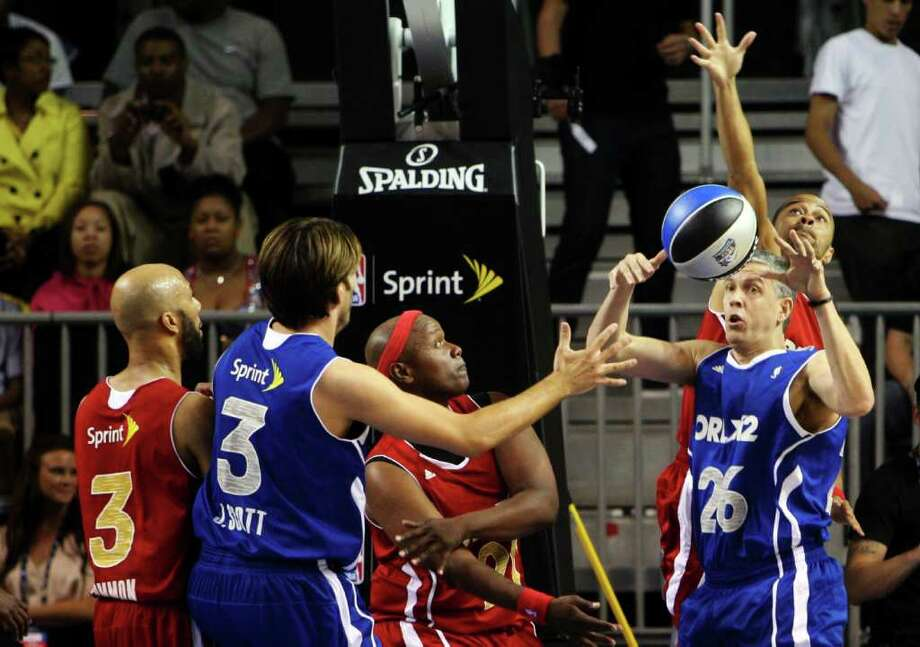 United States Secretary of Education Arne Duncan (26) fights for a loose ball during the NBA All-Star celebrity basketball game, Friday, Feb. 24, 2012, in Orlando, Fla. At left is performer Common (3). (AP Photo/Lynne Sladky) Photo: Associated Press