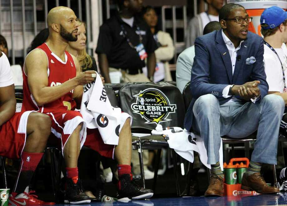 Performer Common, left, and Oklahoma City Thunder's Kevin Durant, right, watch from the bench during the NBA All-Star celebrity basketball game, Friday, Feb. 24, 2012, in Orlando, Fla. Durant was the coach for one of the celebrity teams. (AP Photo/Lynne Sladky) Photo: Associated Press