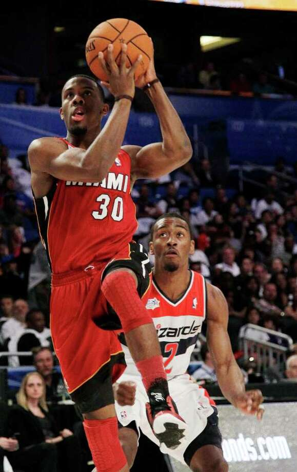 Miami Heat's Norris Cole (30), of Team Shaq, goes for a layup past Washington Wizards' John Wall (2), of Team Chuck, during the NBA All-Star Rising Stars Challenge basketball game in Orlando, Fla. Friday, Feb. 24, 2012. (AP Photo/Chris O'Meara) Photo: Associated Press