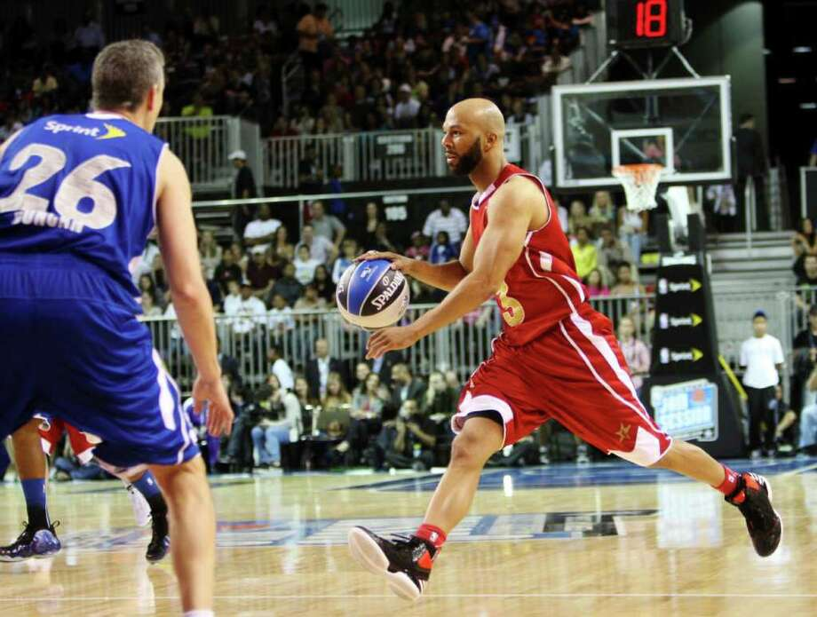 Performer Common, right, dribbles the ball past the United States Secretary of Education Arne Duncan (26) during the NBA All-Star celebrity basketball game, Friday, Feb. 24, 2012, in Orlando, Fla. (AP Photo/Lynne Sladky) Photo: Associated Press