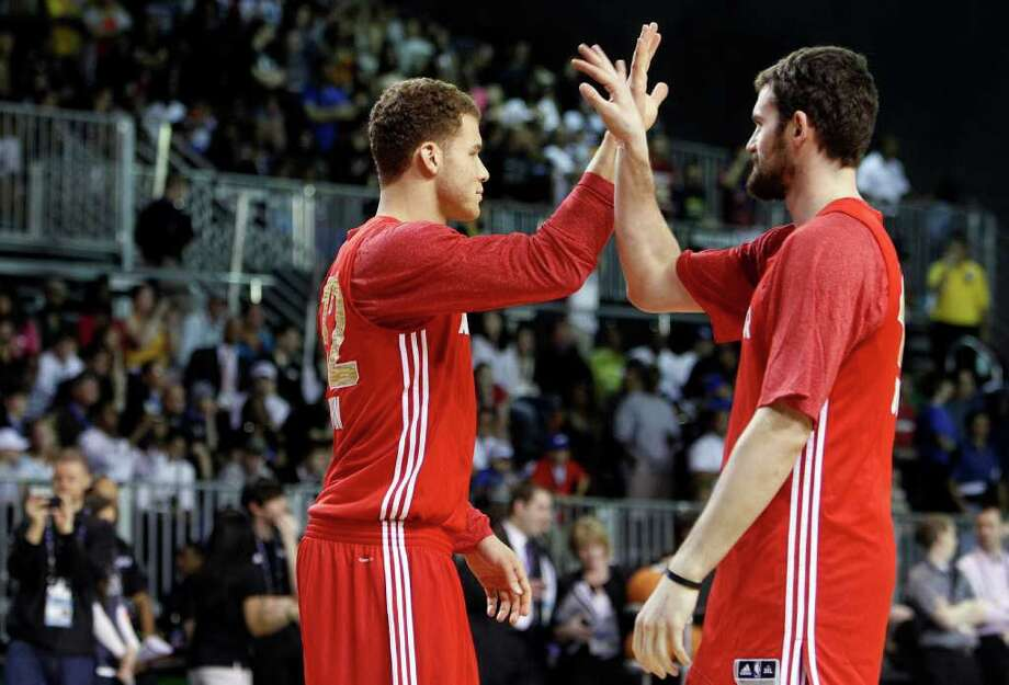Los Angeles Clippers' Blake Griffin, left, high-fives Minnesota Timberwolves' Kevin Love, right, during practice for the NBA All Star basketball game, Saturday, Feb. 25, 2012, in Orlando, Fla. (AP Photo/Lynne Sladky) Photo: Associated Press
