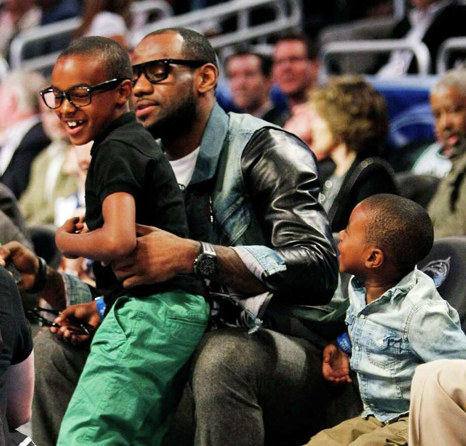 Miami Heat's LeBron James sits with his sons, LeBron Jr., left, and Bryce during the NBA All-Star Shooting Stars basketball competition in Orlando, Fla., Saturday, Feb. 25, 2012. (AP Photo/Lynne Sladky) Photo: Associated Press