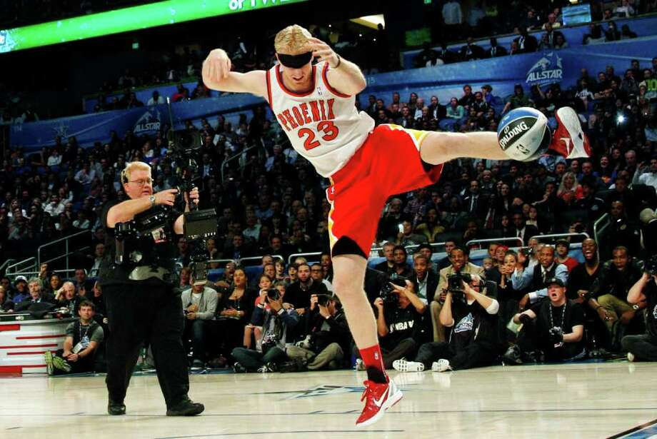 Houston Rockets' Chase Budinger follows through on a blindfolded dunk in honor of former Phoenix Suns' Cedric Ceballos, who performed a blindfolded dunk in 1992, during the NBA basketball All-Star Slam Dunk contest, Saturday, Feb. 25, 2012, in Orlando, Fla. (AP Photo/Lynne Sladky) Photo: Associated Press