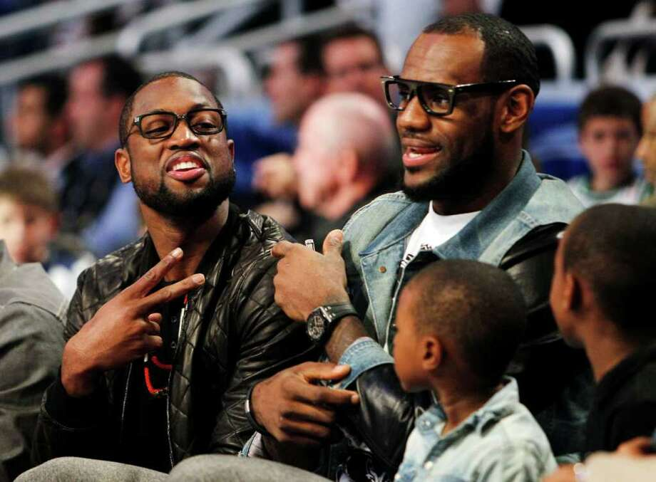 Miami Heat's Dwyane Wade, left, and Lebron James sit courtside with James' sons, LeBron Jr. and Bryce, during the NBA All-Star basketball festivities in Orlando, Fla., Saturday, Feb. 25, 2012. (AP Photo/Lynne Sladky) Photo: Associated Press
