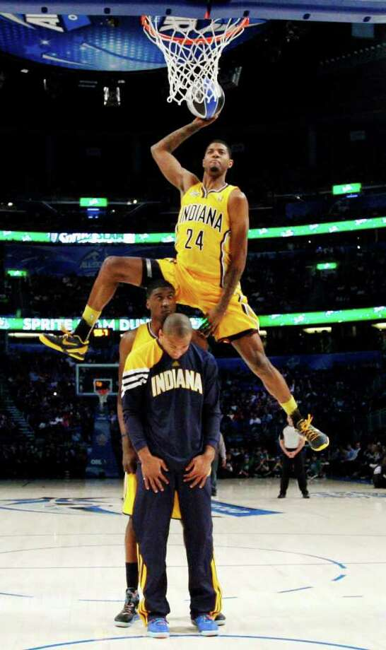 Indiana Pacers' Paul George jumps over two teammates during the NBA basketball All-Star Slam Dunk Contest in Orlando, Fla. Saturday, Feb. 25, 2012. (AP Photo/Jeff Haynes, Pool) Photo: Associated Press