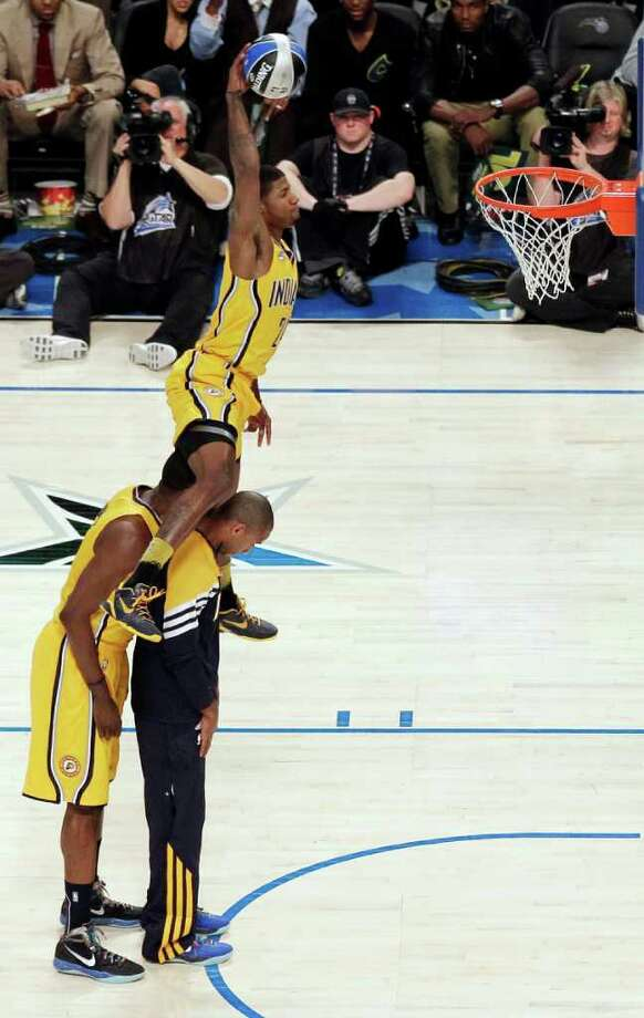 Indiana Pacers' Paul George jumps over two teammates on his attempt during the NBA basketball All-Star Slam Dunk Contest in Orlando, Fla., Saturday, Feb. 25, 2012. (AP Photo/Chris O'Meara) Photo: Associated Press