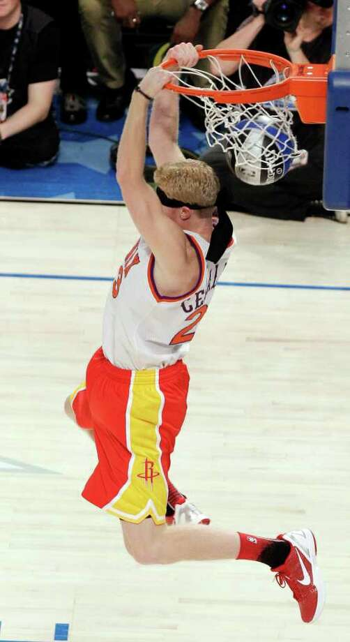 Houston Rockets' Chase Budinger finishes a blindfolded dunk in honor of former Phoenix Suns' Cedric Ceballos, who performed a blindfolded dunk in 1992, during the NBA basketball All-Star Slam Dunk contest, Saturday, Feb. 25, 2012, in Orlando, Fla. (AP Photo/Chris O'Meara) Photo: Associated Press