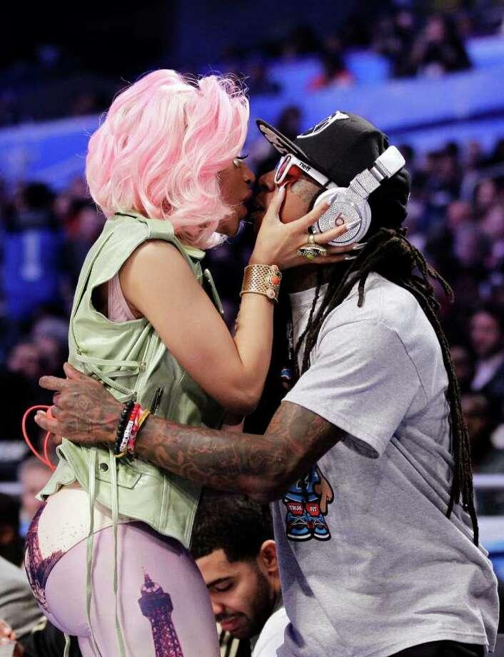 Singer Nicki Minaj, left, greets rapper Lil Wayne during the first half of the NBA All-Star basketball game, Sunday, Feb. 26, 2012, in Orlando, Fla. (AP Photo/Chris O'Meara) Photo: Associated Press
