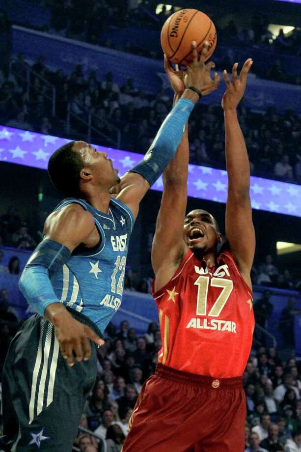 Eastern Conference's Dwight Howard (12), of the Orlando Magic, blocks a shot by Western Conference's Andrew Bynum (17), of the Los Angeles Lakers, during the NBA All-Star basketball game, Sunday, Feb. 26, 2012, in Orlando, Fla. (AP Photo/Chris O'Meara) Photo: Associated Press