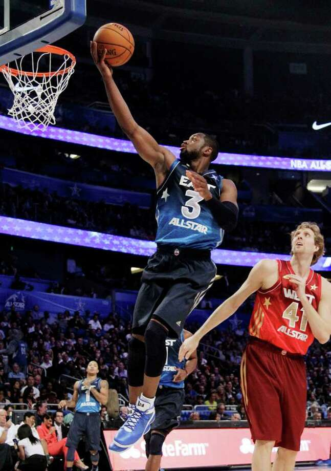 Eastern Conference's Dwyane Wade (3), of the Miami Heat, shoots a layup past Western Conference's Dirk Nowitzki (41), of the Dallas Mavericks, during the second half of the NBA All-Star basketball game, Sunday, Feb. 26, 2012, in Orlando, Fla. (AP Photo/Chris O'Meara) Photo: Associated Press