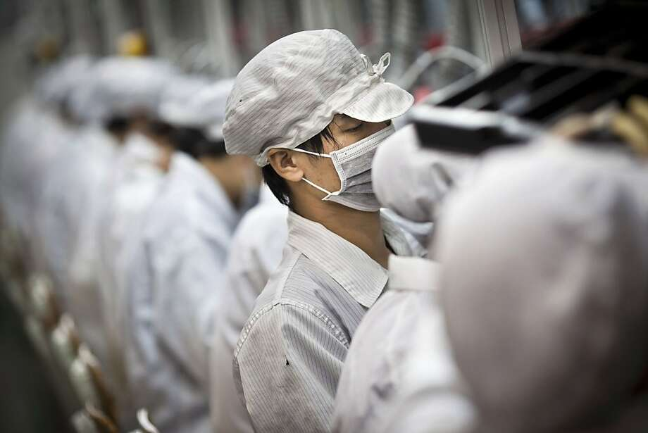 Employees of Hon Hai Precision Industry Co. Ltd. work along a production line in the Longhua Science and Technology Park, also known as Foxconn City, in Shenzhen, China, on Saturday, Sept. 4, 2010. Foxconn Technology Group Chairman Terry Gou cut his long-term growth target for the world's largest contract manufacturer of electronics by 50 percent as demand for Apple Inc. iPhones and iPads fails to offset slowing computer sales. Photographer: Thomas Lee/Bloomberg Employees of Hon Hai Precision Industry Co. Ltd. work along a production line in the Longhua Science and Technology Park, also known as Foxconn City, in Shenzhen, China, on Saturday, Sept. 4, 2010. Foxconn Technology Group Chairman Terry Gou cut his long-term growth target for the world's largest contract manufacturer of electronics by 50 percent as demand for Apple Inc. iPhones and iPads fails to offset slowing computer sales. Photographer: Thomas Lee/Bloomberg Photo: Thomas Lee, Bloomberg