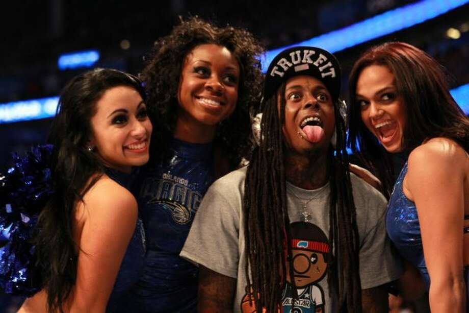 Hip-Hop artist Lil' Wayne poses for a photo with dancers from the Orlando Magic. (Ronald Martinez / Getty Images)