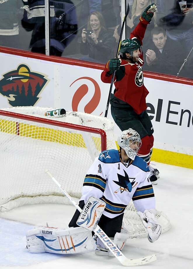 Minnesota Wild's Matt Cullen, top, celebrates a goal by teammate Cal Clutterbuck off San Jose Sharks goalie Thomas Greiss, left, of Germany, in the first period of an NHL hockey game, Sunday, Feb. 26, 2012, in St. Paul, Minn. (AP Photo/Jim Mone) Photo: Jim Mone, Associated Press