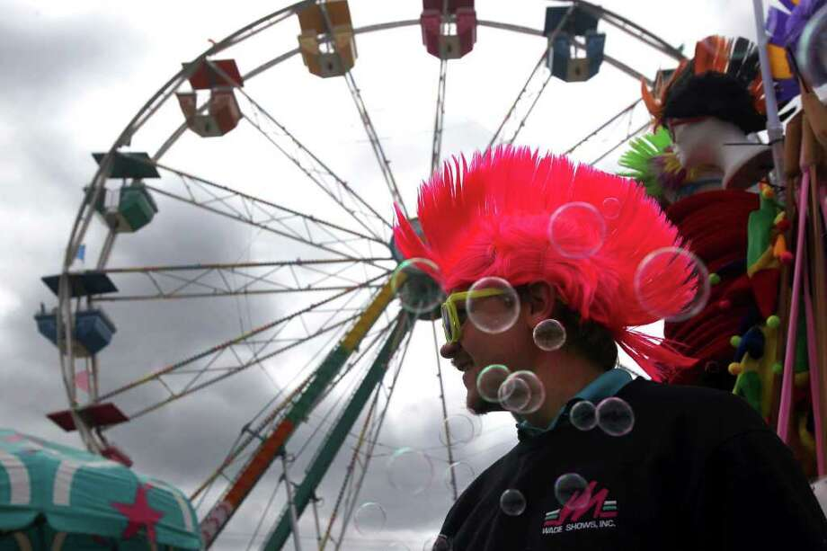 James Hill squirts bubbles from a toy while selling novelties at the midway carnival Sunday February 26, 2012 at the San Antonio Stock Show & Rodeo. Sunday is the last day of the event. John Davenport/San Antonio Express-News Photo: SAN ANTONIO EXPRESS-NEWS