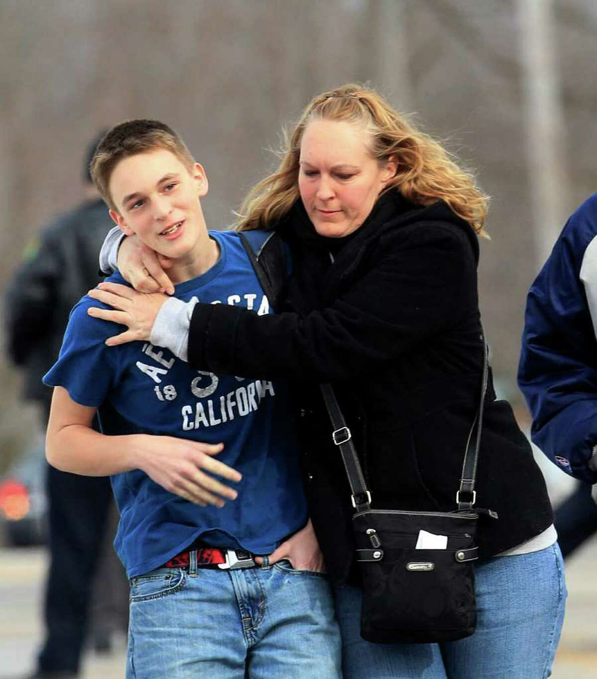 Doug Gasper, a ninth grader at Chardon High School, is hugged by his mother, Sandy, as they leave Maple Elementary School Monday, Feb. 27, 2012, in Chardon, Ohio. Students assembled at Maple Elementary School after a shooting took place at the high school. A gunman opened fire inside the high school's cafeteria at the start of the school day, wounding four students, officials said. A suspect is in custody. (AP Photo/Tony Dejak)