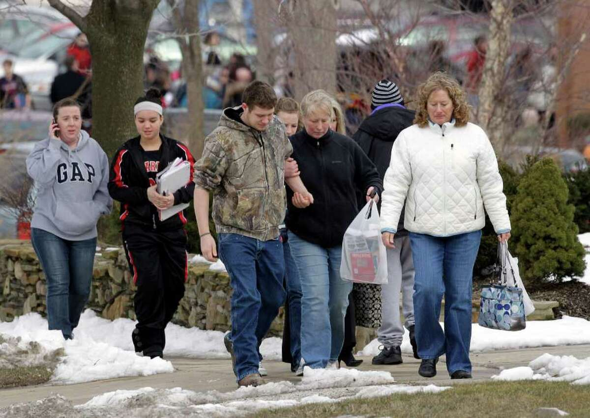 Parents walk past Chardon Middle School with students in Chardon, Ohio Monday, Feb. 27, 2012. The school released students to their parents after a gunman opened fire inside the nearby high school's cafeteria at the start of the school day Monday, wounding four students, officials said. (AP Photo/Mark Duncan)
