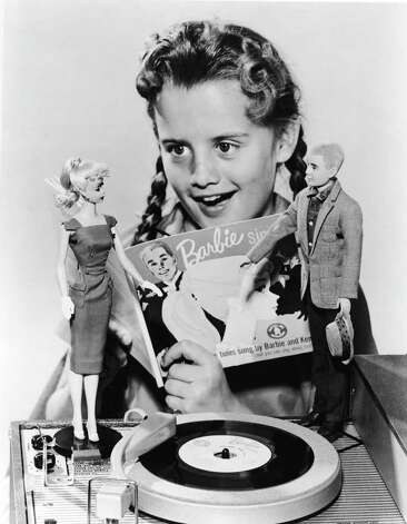"Here, a girl sings along with the record ""Barbie Sings"" in 1961. Barbie and Ken stand on the phonograph. Photo: Hulton Archive, Getty Images / 2004 Getty Images"