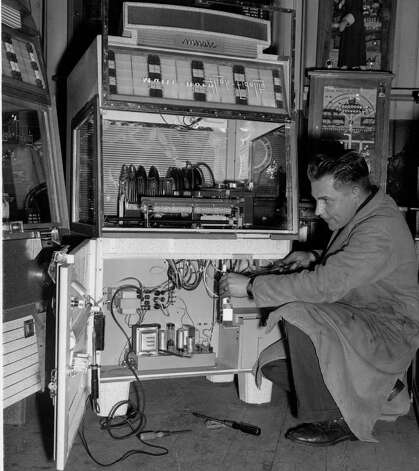 The 1950s popularized jukeboxes. Here, Automatic Musical Industries employee Len Cullum adjusts a jukebox on January 21, 1956 in London. Photo: Fox Photos, Getty Images / Hulton Archive