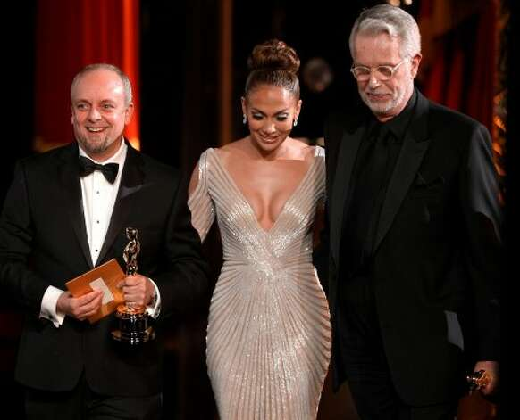 "Mark Coulier, left, and J. Roy Helland, right, winners of the Oscar for best makeup for ""The Iron Lady,"" and Jennifer Lopez walk offstage at the 84th Academy Awards on Sunday, Feb. 26, 2012, in the Hollywood section of Los Angeles. (AP Photo/Chris Carlson) (AP)"