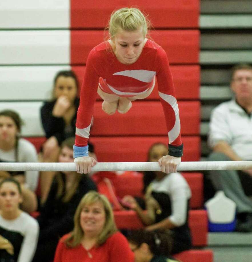 Greenwich High School's Camille Monette, ninth-grade, competes on the high bar during the Class L state gymnastics championships held at Pomperaug High school. Saturady, Feb. 25, 2012 Photo: Scott Mullin / The News-Times Freelance
