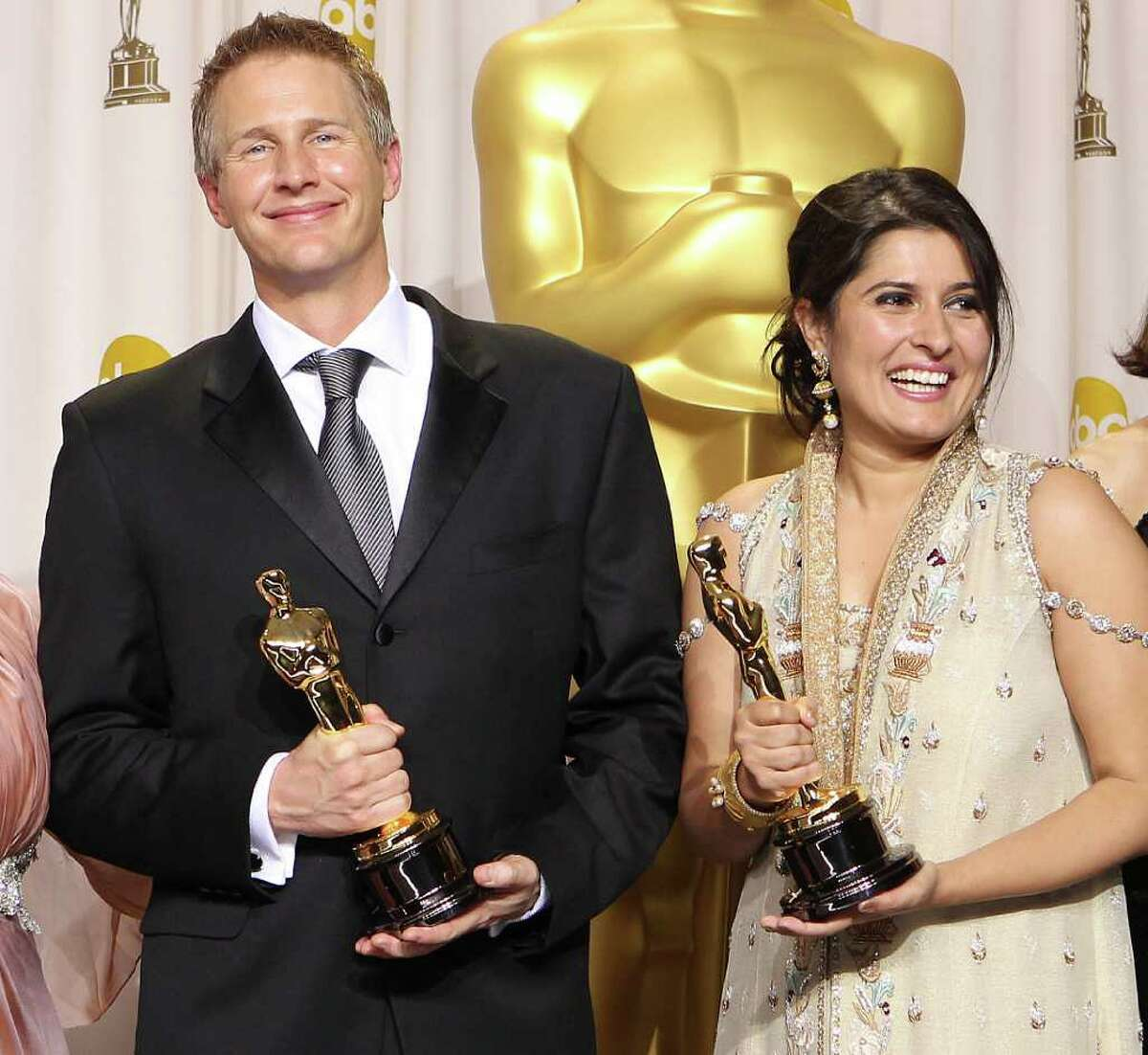Sharmeen Obaid-Chinoy, right, and Daniel Junge pose with their awards for best documentary short for