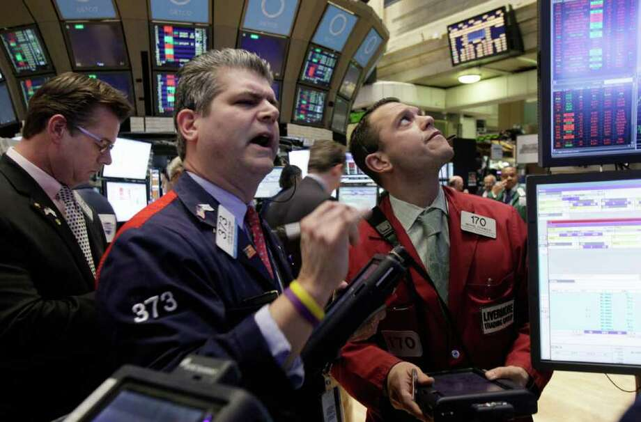 Traders work on the floor of the New York Stock Exchange Monday, Feb. 27, 2012. U.S. stocks pulled back Monday from some of their highest levels in three and a half years. (AP Photo/Richard Drew) Photo: Richard Drew / AP
