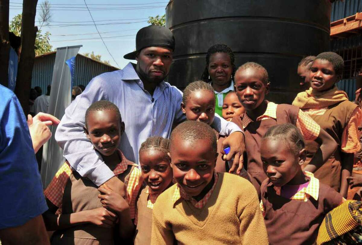 In this Feb. 9, 2012 file photo released by the World Food Programme (WFP), rapper 50 Cent, known as Curtis Jackson, center, visits children in the Kibera slum of Nairobi, Kenya. The rapper-turned-humanitarian flew to Kenya and Somalia with World Food Program earlier this month to witness the effects of hunger firsthand. He has a goal to provide one billion meals to hungry children over the next five years. (AP Photo/World Food Programme, Rose Ogola)