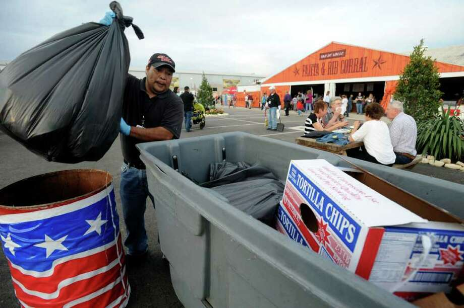 Jose Lopez removes trash from a container in the food court area at the San Antonio Stock Show and Rodeo on Thursday, Feb. 23, 2012. Photo: Billy Calzada, San Antonio Express-News / San Antonio Express-News