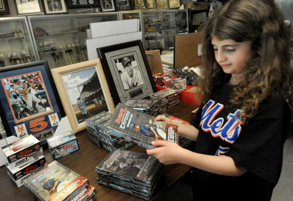 Mackenzie O'Rourke, 7, of Brookfield, looks at baseball card boxes in Dugout Dreams in Danbury, on Aug.25, 2009.