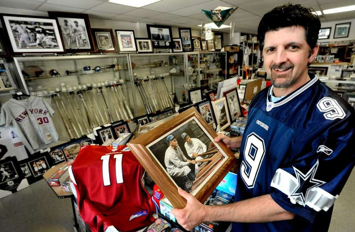 Sean O'Rourke, owner of Dugout Dreams in Danbury, holds vintage memorabilia of Lou Gehrig and Babe Ruth, on Aug.25, 2009.