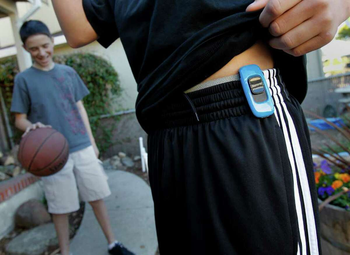 Tristan Wegman shows off the Zamzee device which is so small it is hidden under his t-shirt. His friend Steven Effisimo stands in the background. Tristan Wegman of Redwood City, Calif. uses the Zamzee device to measure his exercise on a daily basis. He also checks his exercise numbers in a fun format online.