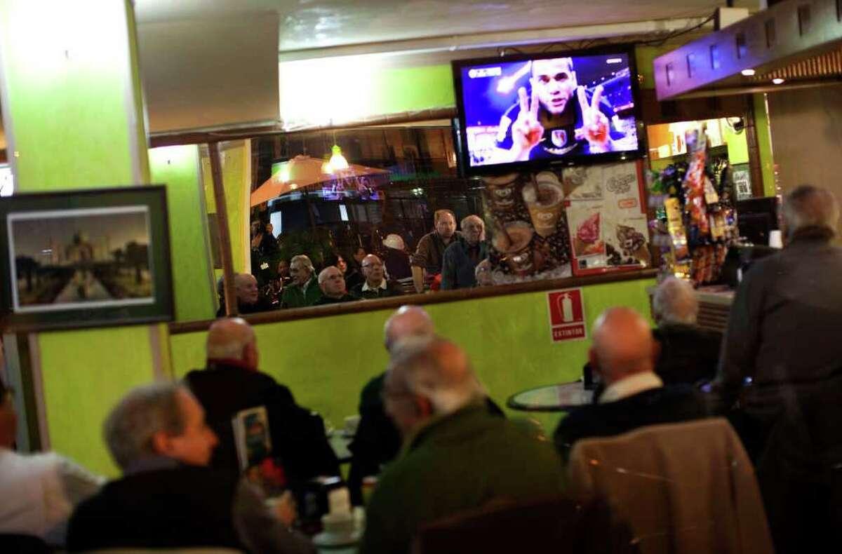 Men watch in a TV how Barcelona's Daniel Alves from Brazil celebrates after scoring a goal against Atletico de Madrid during their Spanish La Liga soccer match in a restaurant in Barcelona, Spain, Sunday Feb. 26, 2012. (AP Photo/Emilio Morenatti)